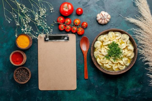 Vista dall'alto deliziosa zuppa di gnocchi con diversi condimenti sulla superficie verde scuro zuppa di carne pasta verdure cibo