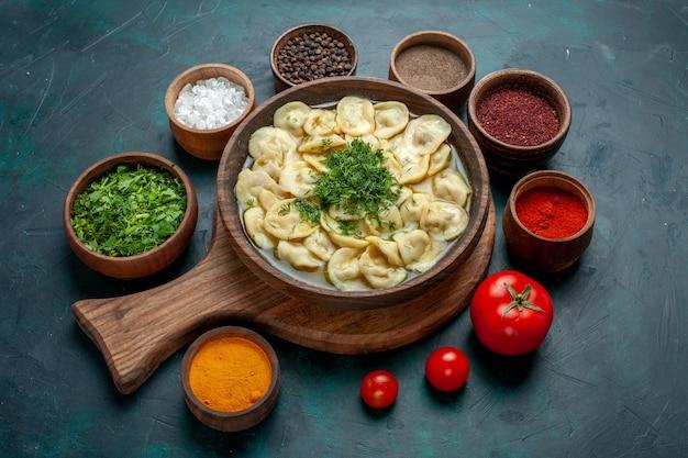 Vista dall'alto deliziosa zuppa di gnocchi con diversi condimenti sulla zuppa di pasta vegetale di carne di cibo da scrivania verde