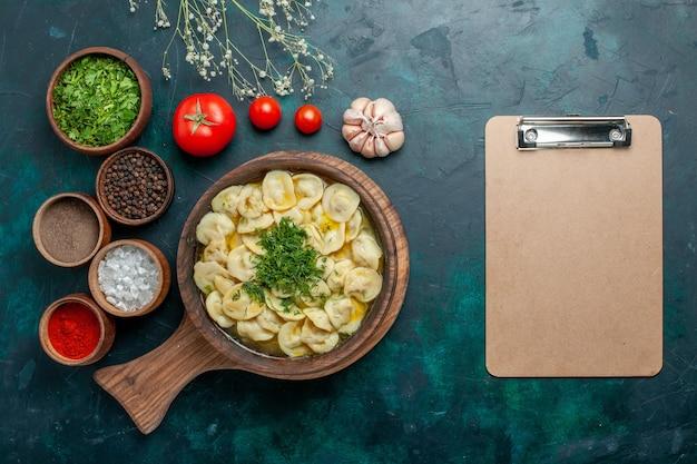 Vista dall'alto deliziosa zuppa di gnocchi con diversi condimenti sulla carne di pasta di verdure di zuppa di cibo superficie verde