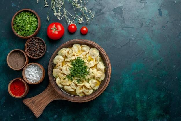 Vista dall'alto una deliziosa zuppa di gnocchi con diversi condimenti sulla zuppa di pasta vegetale di superficie verde