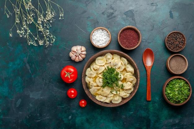 Vista dall'alto deliziosa zuppa di gnocchi con diversi condimenti sulla superficie verde zuppa di carne pasta vegetale cibo