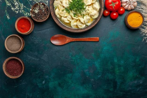 濃い緑色の背景にさまざまな調味料を使ったおいしい餃子スープの上面図肉スープ野菜食品生地