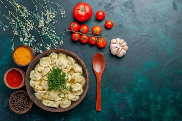 濃い緑色の背景にさまざまな調味料を使ったおいしい餃子スープの上面図スープ生地野菜肉料理