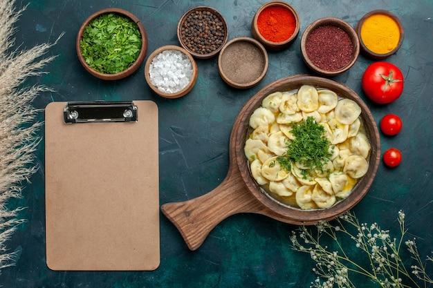 濃い緑色の表面にさまざまな調味料を使ったおいしい餃子スープの上面図食品肉野菜生地スープ