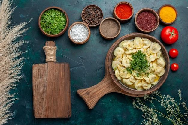 Вид сверху вкусный суп с клецками с разными приправами на зеленой поверхности еда суп из овощного теста