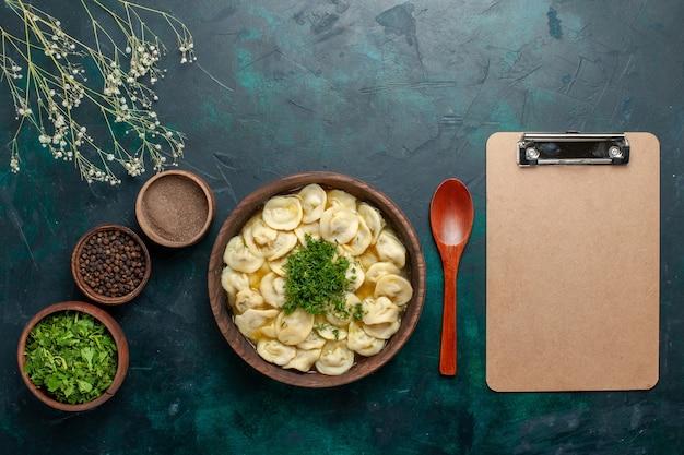 暗い背景に緑とさまざまな調味料を使ったおいしい餃子スープの上面図スープ生地野菜料理