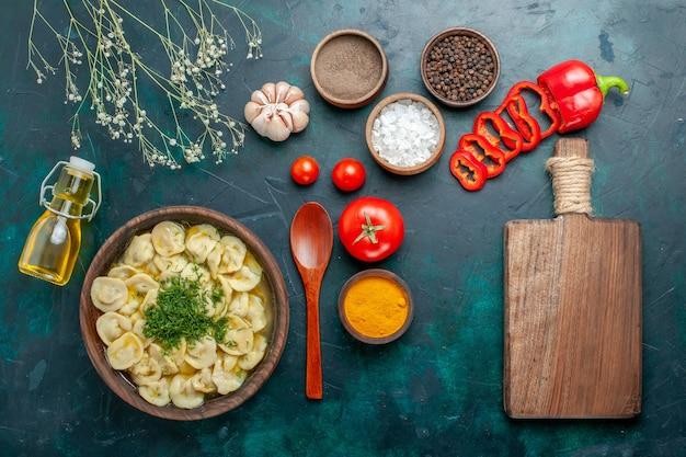 Vista dall'alto deliziosa zuppa di gnocchi con condimenti di olio e pomodori sulla carne di zuppa di farina di cibo superficie verde