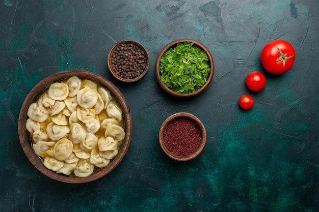濃い緑色の背景に調味料が入ったおいしい餃子スープの上面図食品肉野菜スープ生地