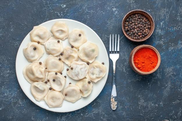 Vista dall'alto di deliziosi gnocchi all'interno del piatto insieme al pepe sul buio, pasta pasto cena cibo carne calorica