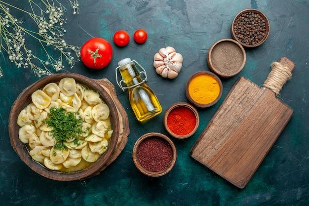 Вид сверху вкусные пельмени с разными приправами и маслом на темно-зеленой поверхности тесто для еды мясо овощи ужин выпечка
