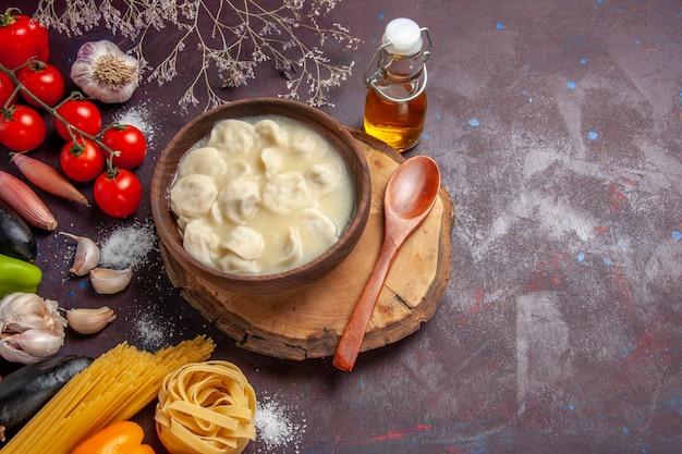 Вид сверху вкусные пельмени с разными приправами на темном столе, мясном обеденном соусе, тесте
