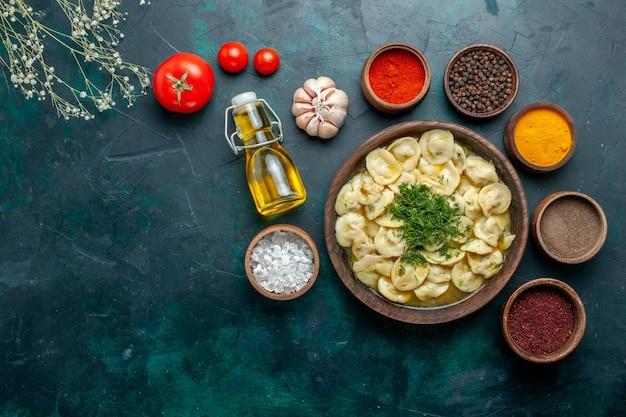 Вид сверху вкусные пельмени с разными приправами на темно-зеленом тесте для еды, мясном овощном обеденном тесте