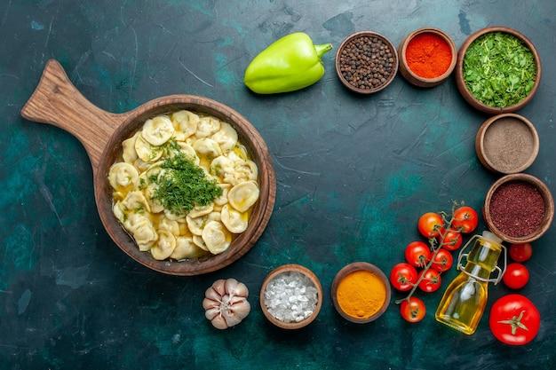 Вид сверху вкусные пельмени с разными приправами на темно-зеленой поверхности пищевой ингредиент продукт тесто мясо овощ