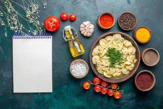 Вид сверху вкусные пельмени с разными приправами на темно-зеленой поверхности обеденное тесто из мяса и овощей