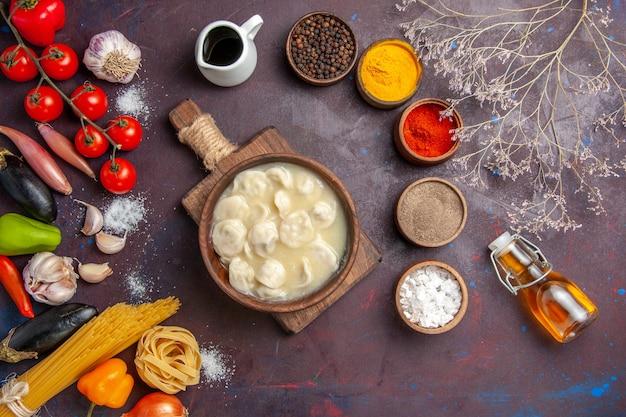 Вид сверху вкусные пельмени с приправами на темном фоне, мясная еда, ужин, соус, тесто