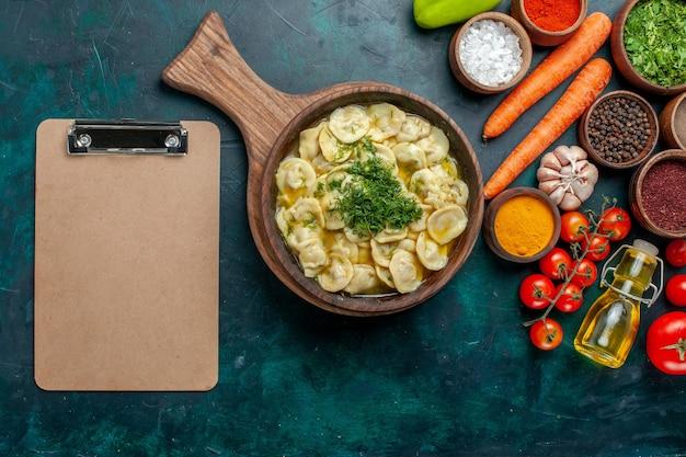 濃い緑色の表面の食品成分製品生地肉野菜に野菜とさまざまな調味料を入れたおいしい餃子の上面図