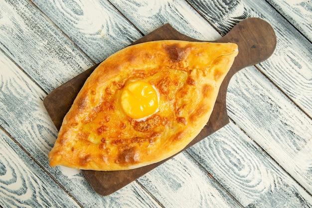 Vista dall'alto delizioso pane all'uovo cotto su spazio rustico grigio