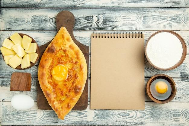 灰色の素朴な机の上で焼いた上面図おいしい卵パン