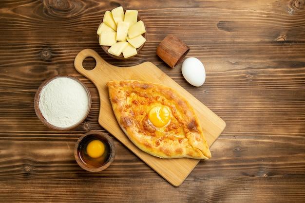 茶色の木製の机の上で焼いた上面図おいしい卵パン