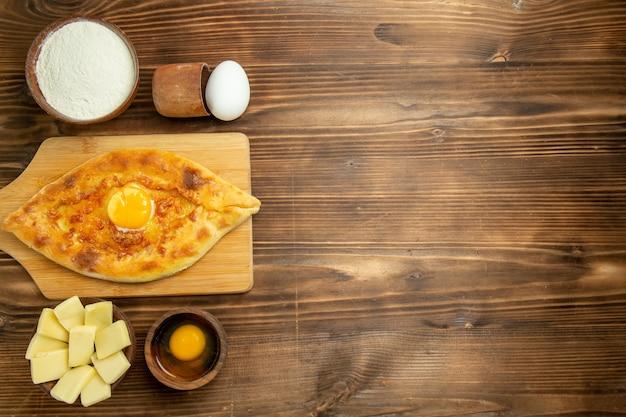 上面図茶色の木製テーブルパンパンで焼いたおいしい卵パン朝食の卵を焼く