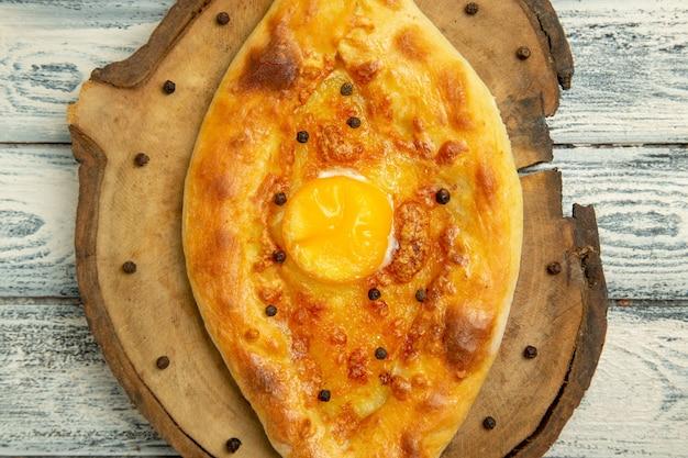 Vista dall'alto delizioso pane all'uovo cotto su rustico spazio grigio