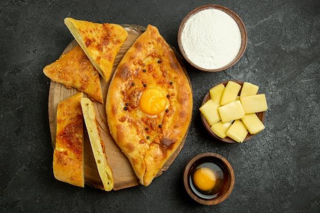 Vista dall'alto delizioso pane all'uovo cotto a fette con formaggio e farina sullo spazio grigio
