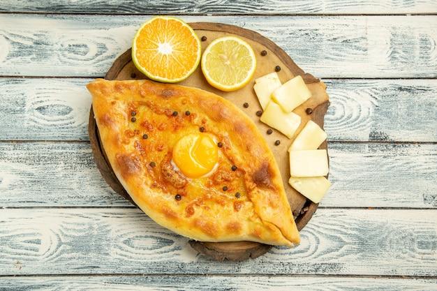 素朴な机の上でチーズで焼いたトップビューおいしい卵パン