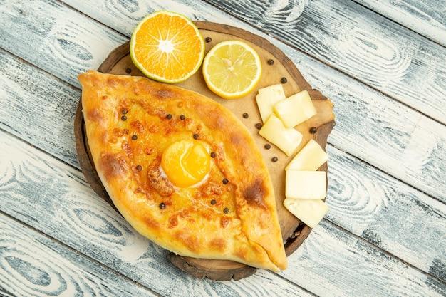 Vista dall'alto delizioso pane all'uovo cotto con formaggio sulla scrivania rustica
