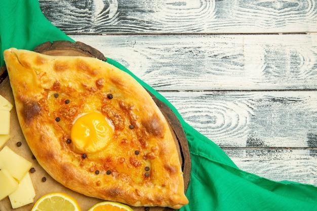 Vista dall'alto delizioso pane all'uovo cotto con formaggio su una scrivania grigia rustica