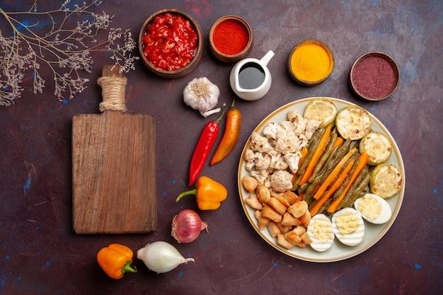 Vista dall'alto delizioso pasto a base di uova con verdure cotte e condimenti in uno spazio buio