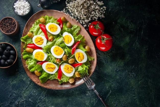 トップビューおいしいエッグサラダは、暗い背景にオリーブとグリーンサラダで構成されています