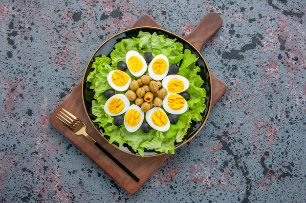 トップビューおいしいエッグサラダグリーンサラダと明るい背景のオリーブ
