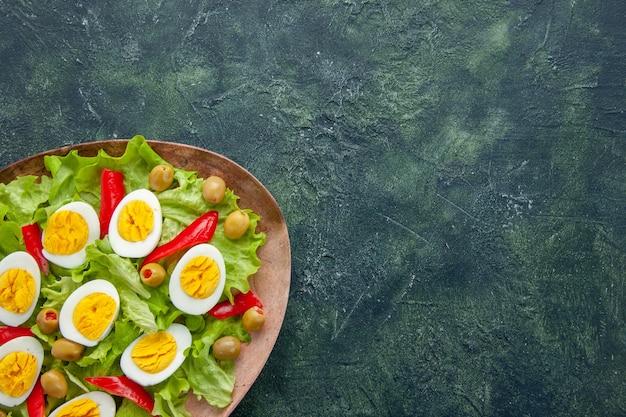 Vista dall'alto deliziosa insalata di uova con insalata verde e olive su sfondo blu scuro