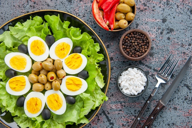 Top view delicious egg salad with seasonings and olives on light background