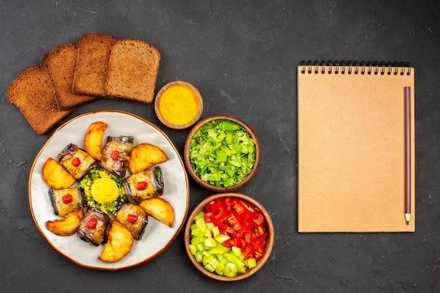 トップビューおいしいナスロールベイクドポテトとパンを使った調理済みの料理暗い背景の料理料理ポテトフライベイク