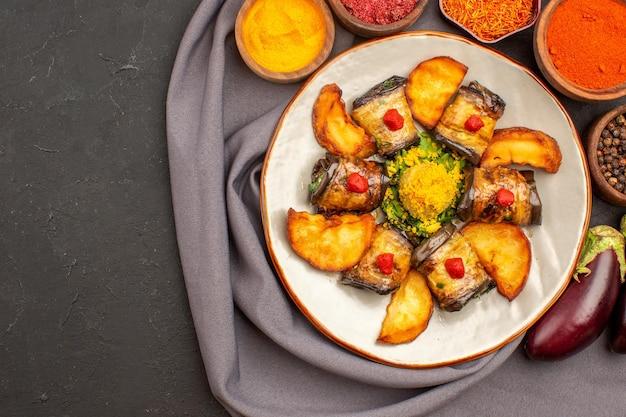 Вид сверху вкусные рулетики из баклажанов приготовленное блюдо с печеным картофелем и приправами на темном фоне еда блюдо еды приготовление картофеля