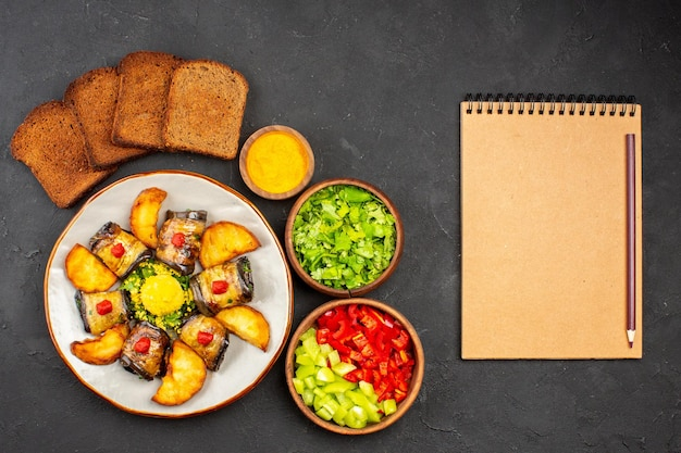 Vista dall'alto deliziosi involtini di melanzane piatto cotto con patate al forno e pane sullo sfondo scuro piatto che cucina cibo fritto di patate al forno