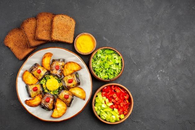 Vista dall'alto deliziosi involtini di melanzane piatto cotto con patate al forno su uno sfondo scuro piatto che cucina cibo fritto di patate al forno