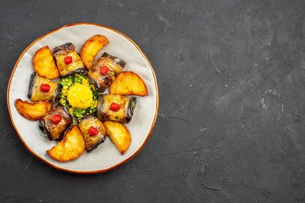 Vista dall'alto deliziosi involtini di melanzane piatto cucinato con patate al forno sullo sfondo scuro piatto da pasto cucinare cibo cuocere patate fritte