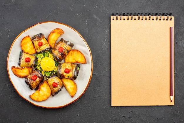 Vista dall'alto deliziosi involtini di melanzane piatto cucinato con patate al forno su piatto da tavolo scuro cucinare cibo cuocere patate fritte
