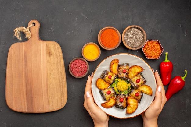 Вид сверху вкусные рулетики из баклажанов приготовленное блюдо с печеным картофелем на темно-сером фоне блюдо из картофеля еда ужин приготовление еды