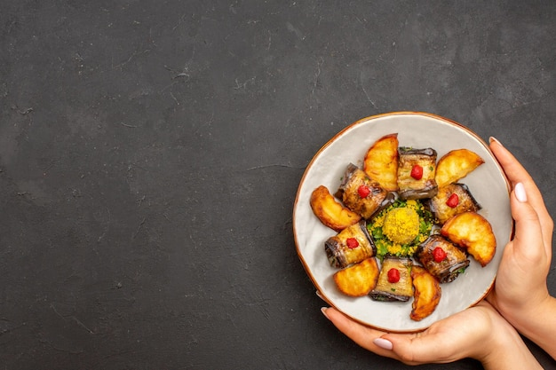 Вид сверху вкусные рулетики из баклажанов приготовленное блюдо с печеным картофелем на темном фоне блюдо из картофеля еда ужин еда приготовление