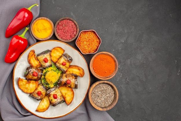 Vista dall'alto deliziosi involtini di melanzane piatto cotto con patate al forno e condimenti su sfondo scuro piatto cibo cucina patata pasto meal