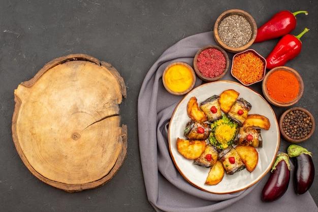 Vista dall'alto deliziosi involtini di melanzane piatto cucinato con patate al forno e condimenti su fondo scuro piatto da cucina di patate