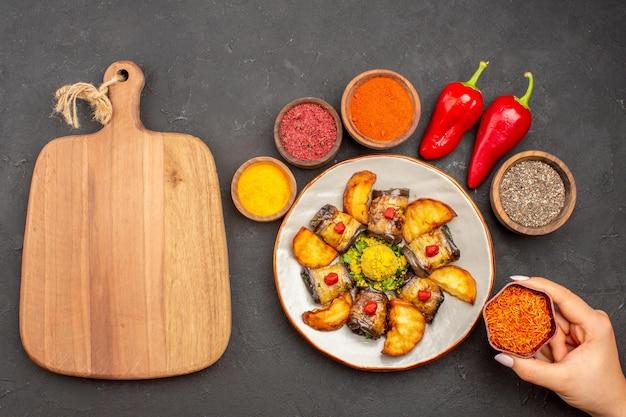 Vista dall'alto deliziosi involtini di melanzane piatto cucinato con patate al forno e condimenti su sfondo scuro piatto di patate cena cucina cibo