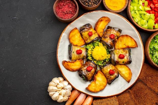 トップビューおいしいナスロール調理済みの皿にジャガイモとパンのローフを暗い背景に調理する食品フライドポテトベイクドポテト