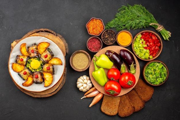 상위 뷰 맛있는 가지 롤은 어두운 배경에 감자와 야채를 곁들인 요리 요리 음식 요리 감자 튀김을 굽습니다