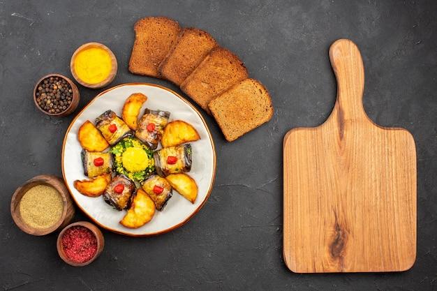 상위 뷰 맛있는 가지 롤은 어두운 배경 요리에 감자 빵과 조미료를 곁들인 요리 음식 감자 튀김 베이킹을 요리합니다.