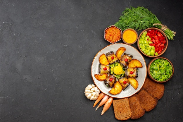 Top view delicious eggplant rolls cooked dish with potatoes and bread loafs on dark background cooking food fry dish bake potato