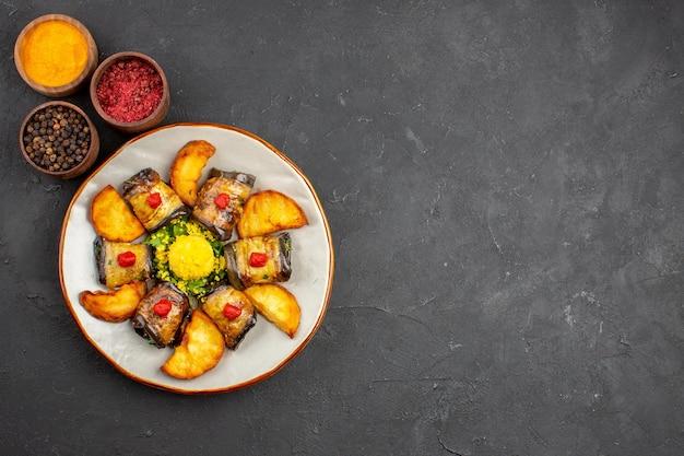 Vista dall'alto deliziosi involtini di melanzane piatto cucinato con patate e condimenti su fondo scuro piatto che cucina cibo fritto di patate al forno